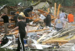 Globe/Roger Nomer Rescuers look through a damaged building near 15th and Range Line on Sunday evening.